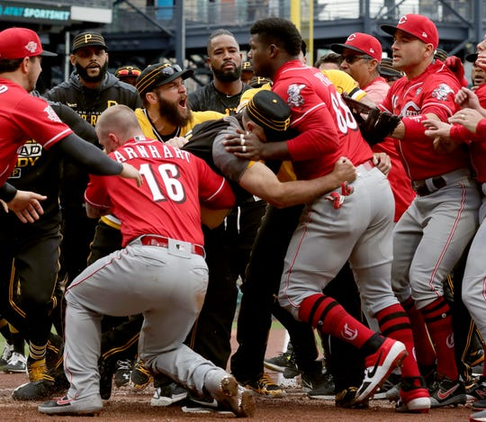 Cincinnati Reds' Yasiel Puig (66) is restrained by Pittsburgh Pirates bench coach Tom Prince, in the middle of a bench clearing brawl during the fourth inning of a baseball game in Pittsburgh, Sunday, April 7, 2019.