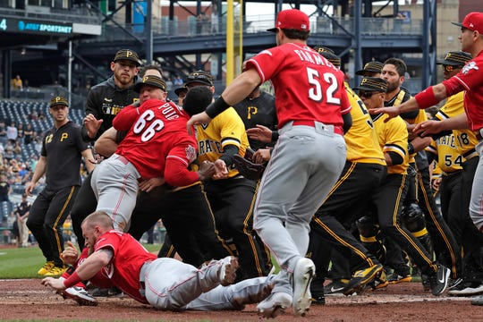 Cincinnati Reds' Yasiel Puig (66) pulls away from Tucker Barnhart (16) as he attempts to re-enter a bench clearing during the fourth inning of a baseball game against the Pittsburgh Pirates in Pittsburgh, Sunday, April 7, 2019.