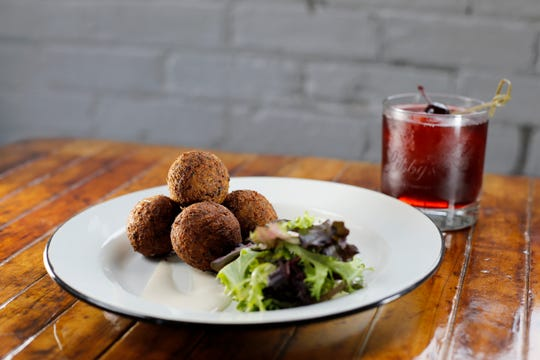 The Goetta Hush Puppies appetizer with a Cherry Cheerwine Bourbon Slush at Libby's Southern Comfort in Covington, Ky., on Monday, April 8, 2019.