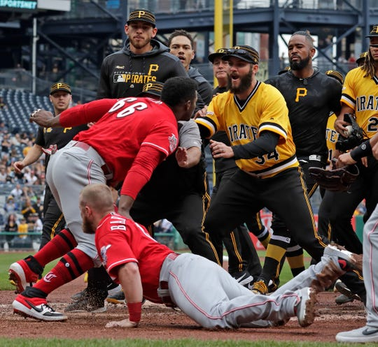 Cincinnati Reds' Yasiel Puig (66) pulls away from Tucker Barnhart (16) and runs into Pittsburgh Pirates bench coach Tom Prince, center, as he attempts to re-enter a bench clearing during the fourth inning of a baseball game against the Pittsburgh Pirates in Pittsburgh, Sunday, April 7, 2019.