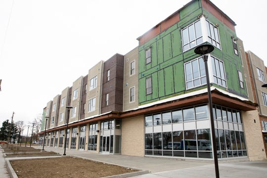 Mixed-income apartments ride above storefronts on Reading Road in the new Avondale Town Center. A grocery and variety store will open to the west onto a parking lot in the rear.