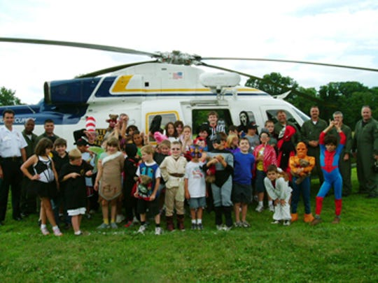 Okee Sunokee campers gather around a State Police helicopter that dropped in for a visit.