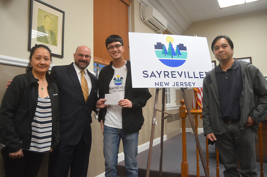 Kevin Polston of NAP's Riverton development, which coordinated and sponsored the logo contest at Sayreville War Memorial High School, presents Patrick Pusung and his parents a $1,000 scholarship.