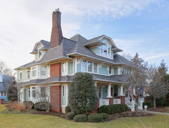 This five-bed, four-bath custom Colonial home features detailed craftsmanship and curb appeal on a corner lot.