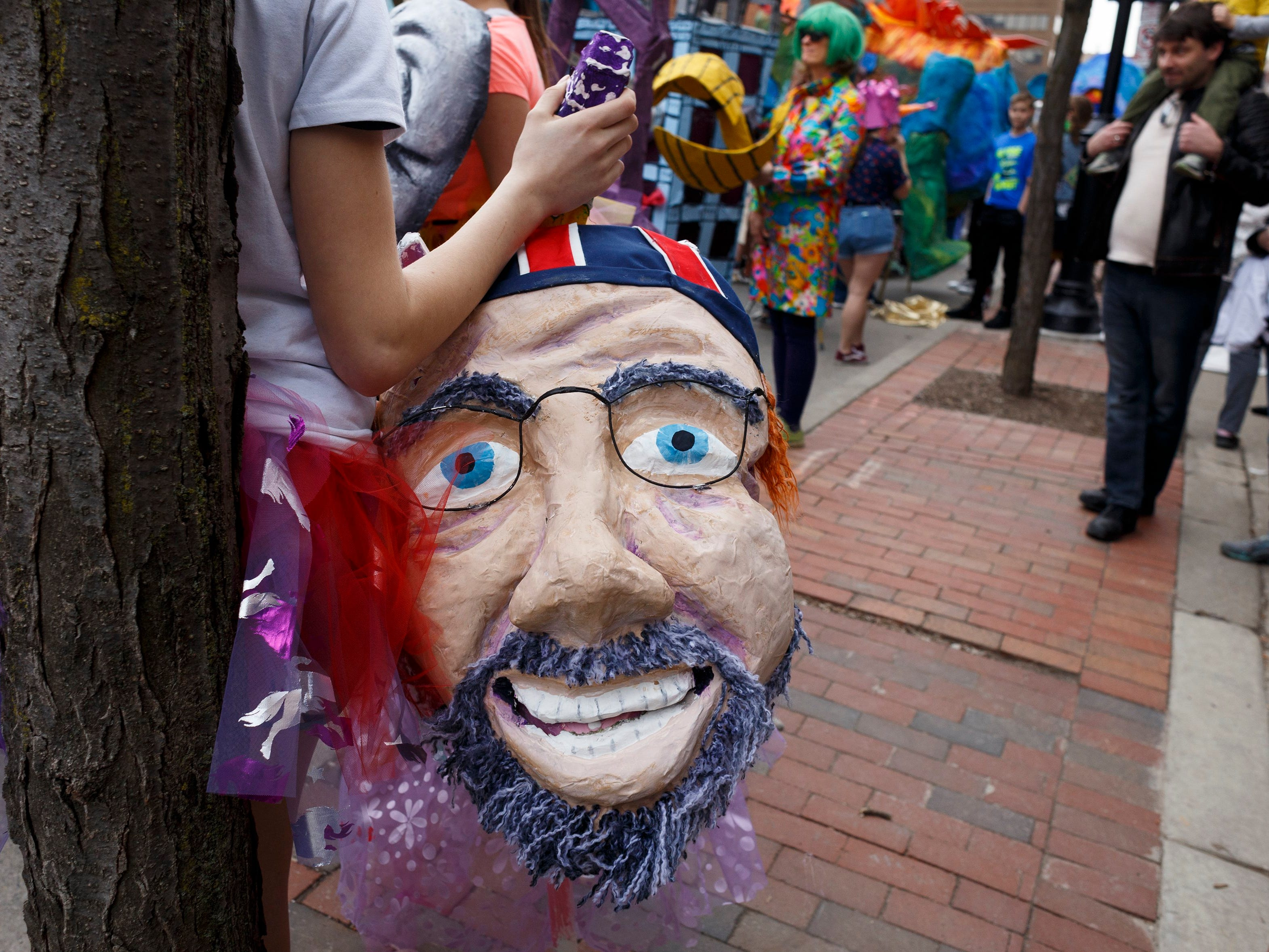 Mikala Sposito, 14, of Dexter holds the head of her puppet before the start of the annual FestiFools parade on Sunday, April 7, 2019 on South Main Street in downtown Ann Arbor.