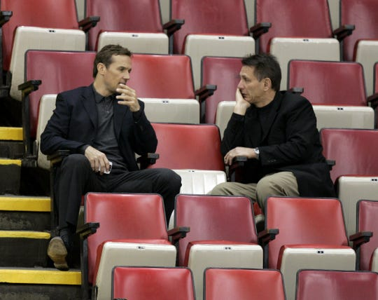 Red Wings great Steve Yzerman, left, and general Ken Holland talks as they watch practice Monday, April 9, 2007, at Joe Louis Arena.