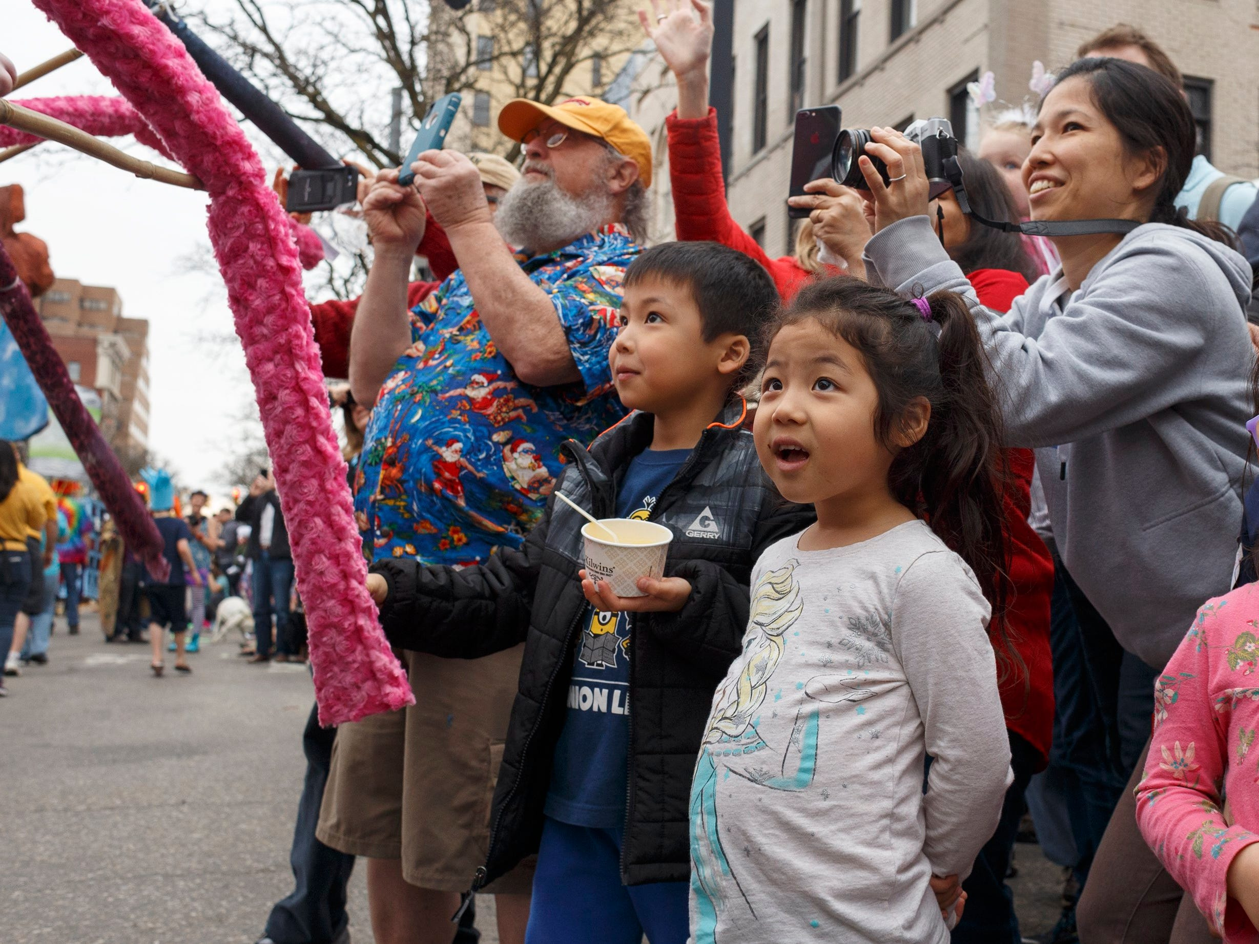 Siblings Hara, 7, left, and Iroha, 5, watch as puppets pass during the annual FestiFools parade on Sunday, April 7, 2019 on South Main Street in downtown Ann Arbor.