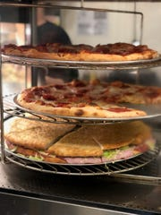 The deli slice, $3 each, sits in a pizza warmer inside the store.