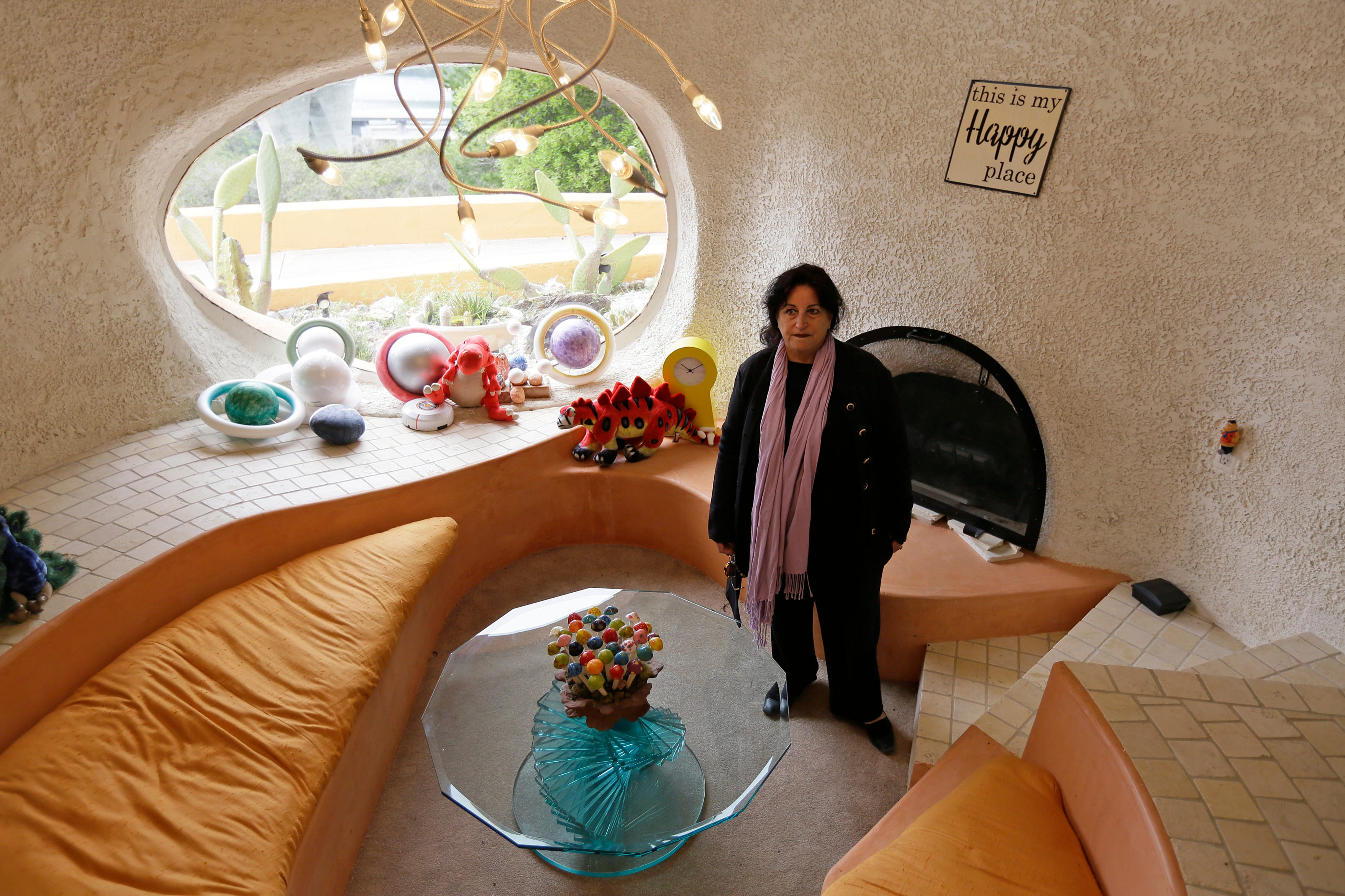 """Attorney Angela Alioto looks over a sunken room called """"The Happy Place,"""" inside the Flintstone House in Hillsborough, Calif."""