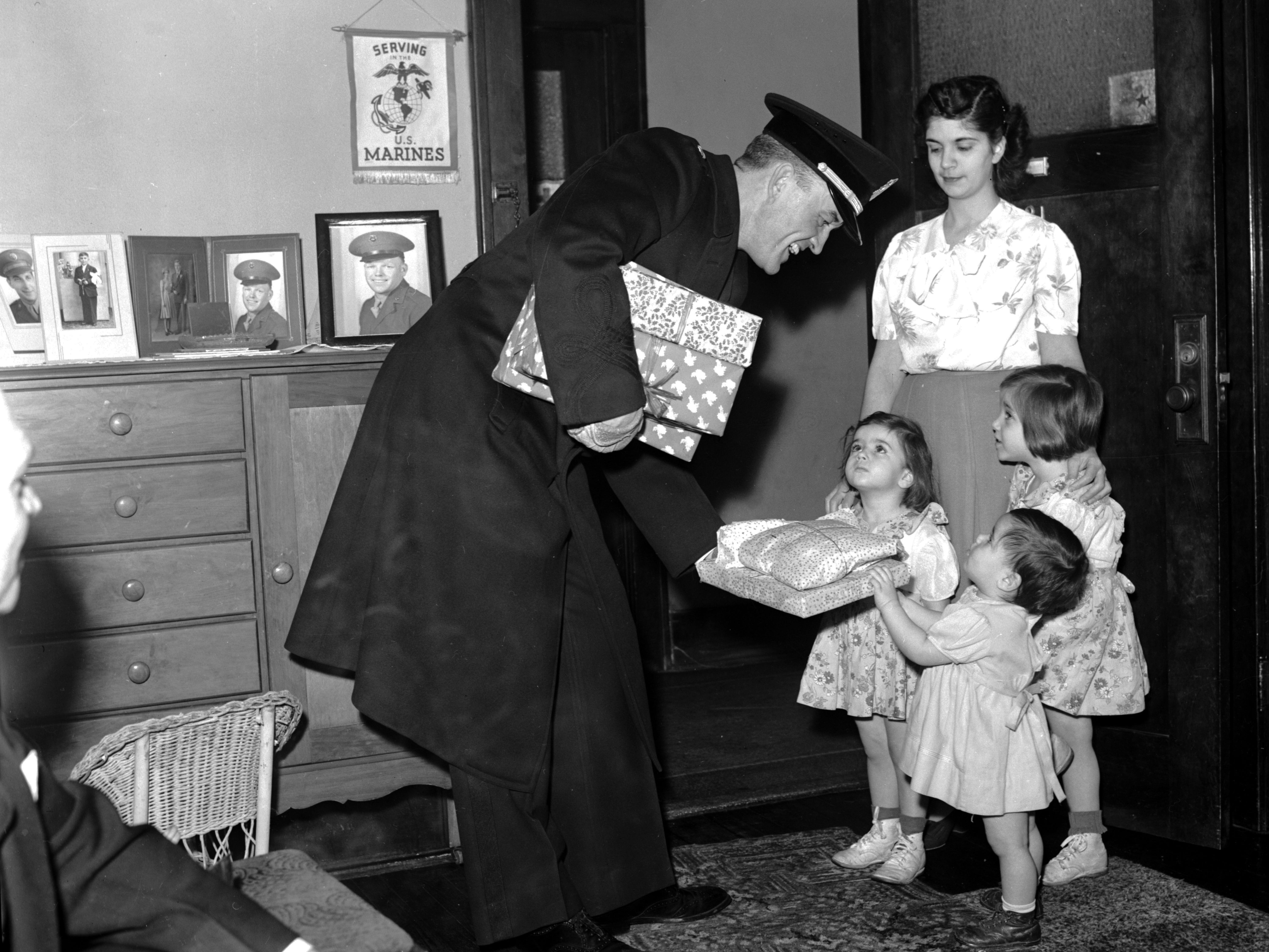 A man in uniform delivers Christmas presents to three children on behalf of the Old Newsboys charity on Dec. 12, 1944.