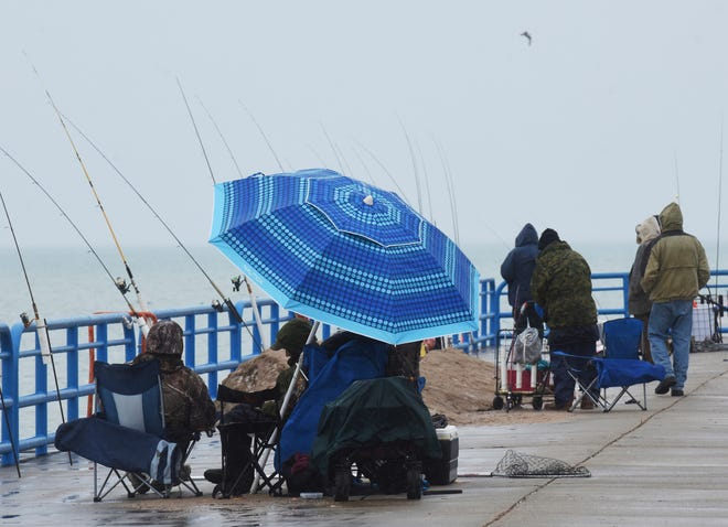 Fishermen brave rainy weather late last week as they work the waters of Lake Michigan in St. Joseph. Michigan weather this week is expected to include a bit of everything: warm temps, sun, rain and, maybe, snow.