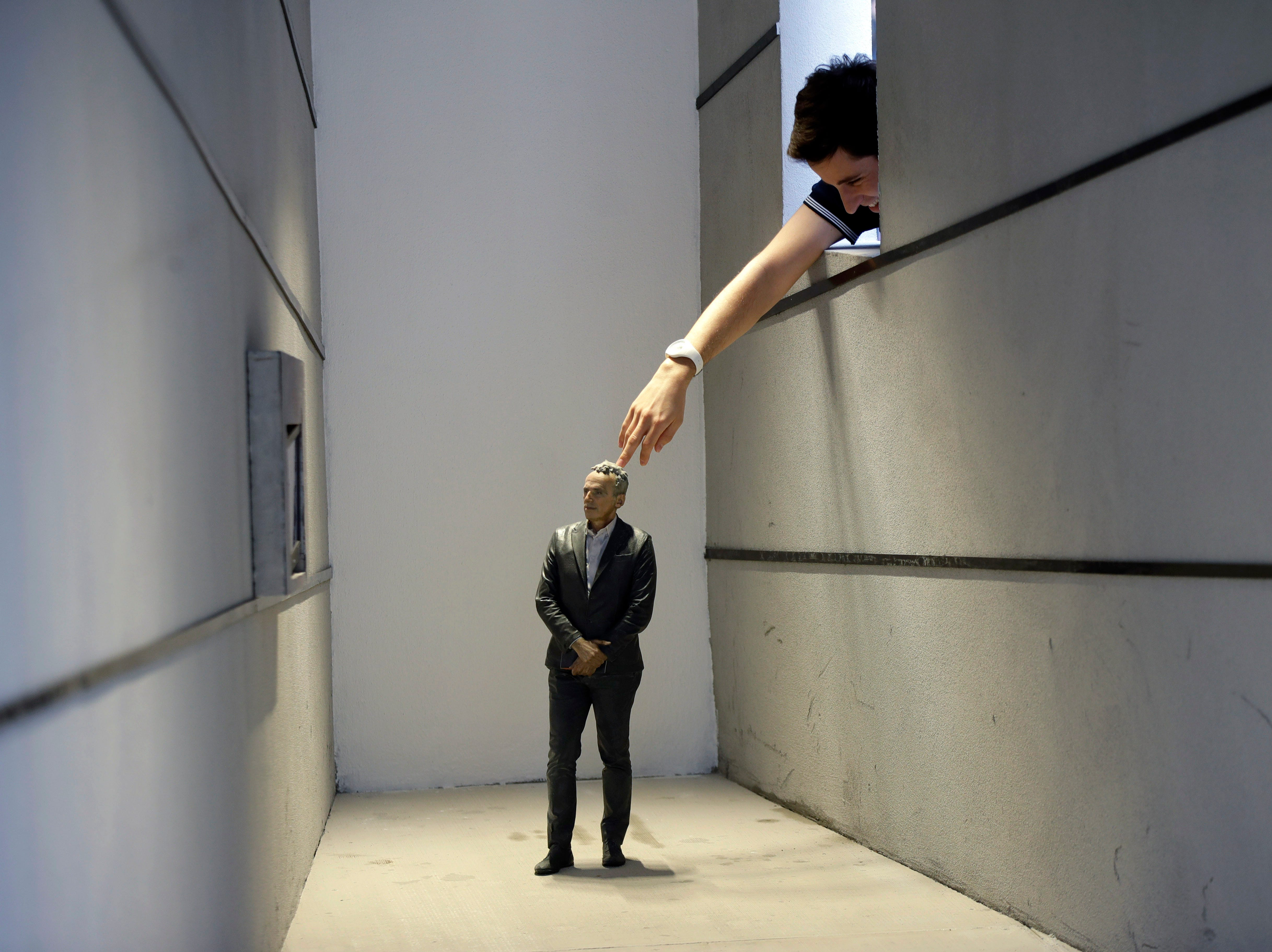 A visitor touches a reproduction of a man of 'Human Proportions' installation by architect Massimo Iosa Ghini displayed on the occasion of the Fuorisalone exhibition, at the Furniture fair, in Milan, Italy, Monday, April 8, 2019. The Milan Furniture fair week is taking place in various locations from April 9-14, 2019.