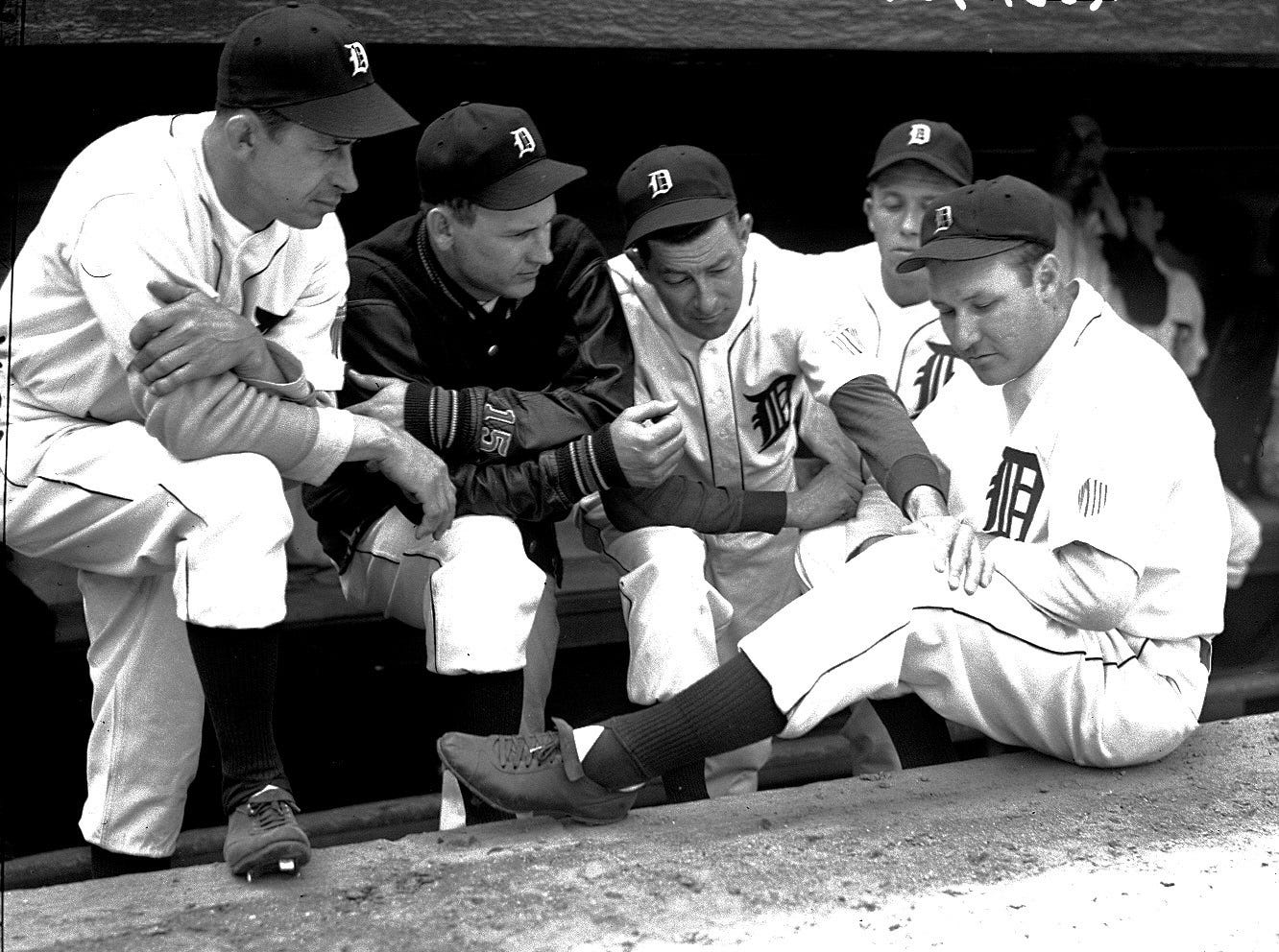 Tigers first baseman Rudy York  shows his knee, which kept him out of the Army, to a group of teammates, including Chuck Hostetler, Dizzy Trout, Doc Cramer and Jimmy Outlaw.