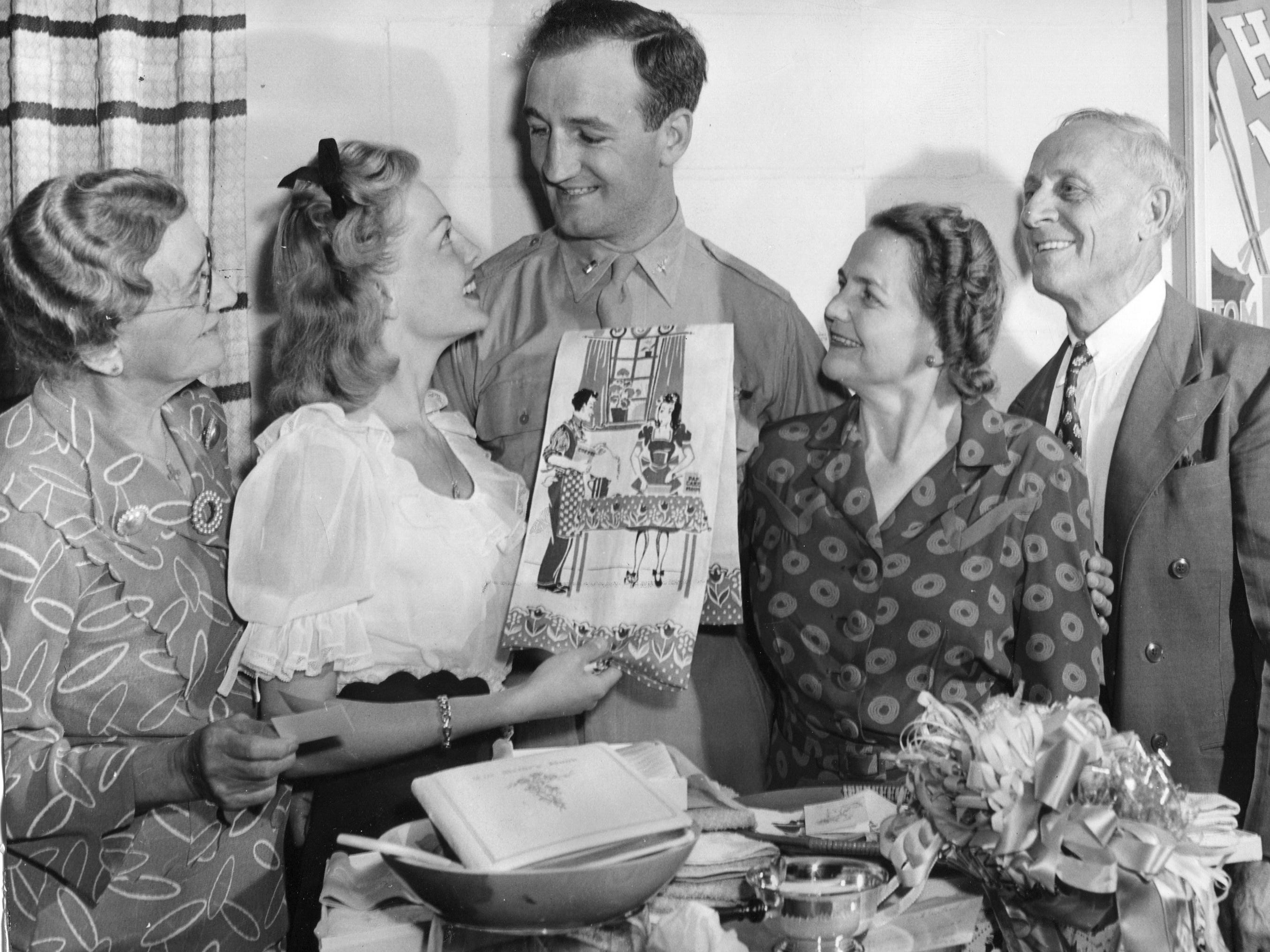 Tom Harmon, the former Heisman Trophy winner at the University of Michigan,  opens wedding shower gifts with his fiancé Elyse Knox in 1944.  Harmon was a pilot in World War II, surviving a crash in South America and then being shot down over China.