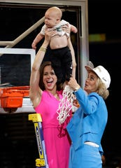 Baylor coach Kim Mulkey, right, watches as her daughter and assistant coach Makenzie Fuller holds up her 6-month-old son Kannon Reid Fuller, after the Final Four championship game. Baylor won 82-81.