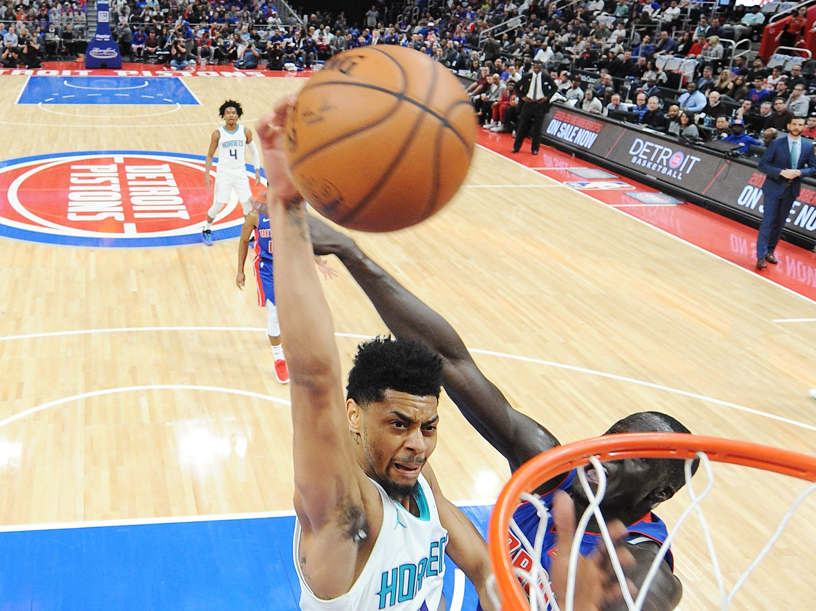 Hornets' Jeremy Lamb is fouled by Pistons' Thon Maker on his dunk attempt in the second quarter.  The Hornets defeated the Pistons 104-91, Sunday, April 7, 2019 at Little Caesars Arena in Detroit, Michigan.