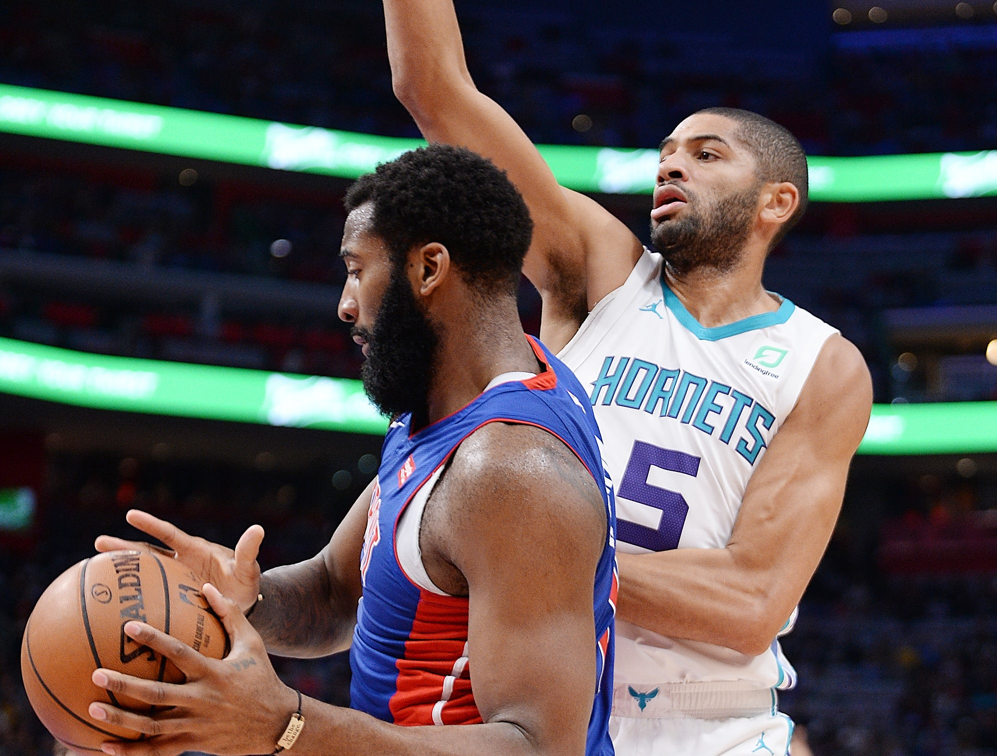 Pistons' Andre Drummond drives around Hornets' Nicolas Batum in the first quarter.