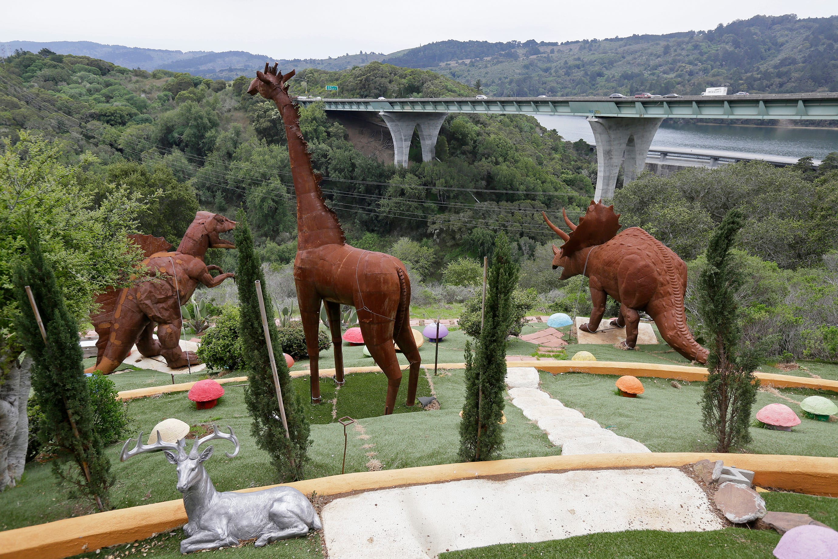In this photo taken Monday, April 1, 2019, dinosaurs and other figures stand outside the Flintstone House overlooking Interstate 280 in Hillsborough, Calif.