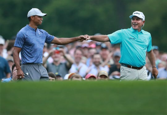 Tiger Woods and Fred Couples exchange a fist bump after they both hit their tee shots close on the 12th hole.