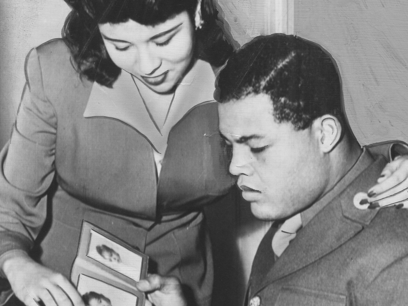Heavyweight boxing champion Joe Louis, wearing sergeant's stripes, looks at family photos with his wife, Marva Trotter. He served in the Army for 45 months during the war, mostly boxing in exhibition bouts and visiting hospitals across the U.S. and overseas.
