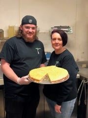 Co-owner Aaron Skinner and the store's general manager Tina Wheeler show off a full tray of deli slices.