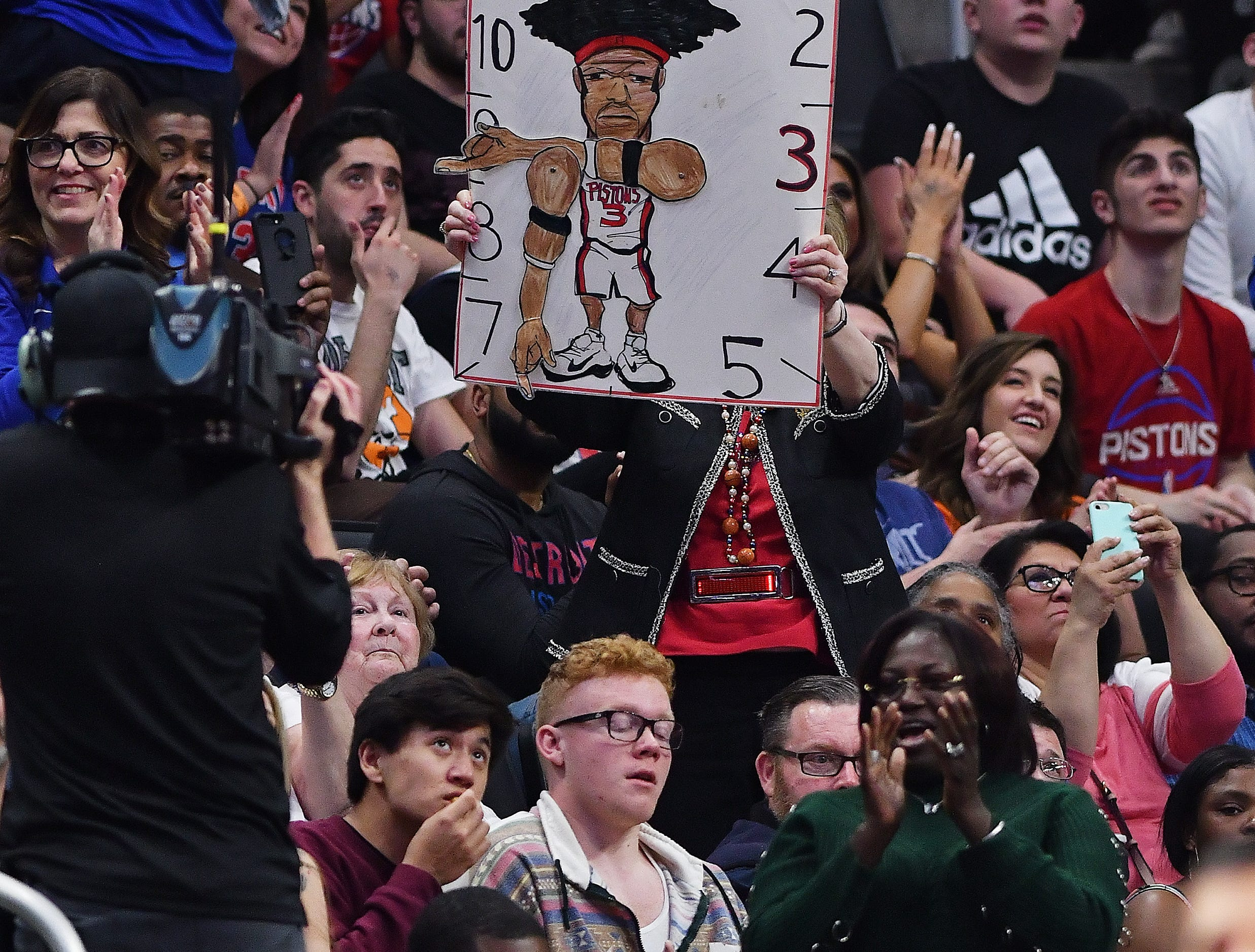 A fan holds a Ben Wallace clock poster in the second quarter.