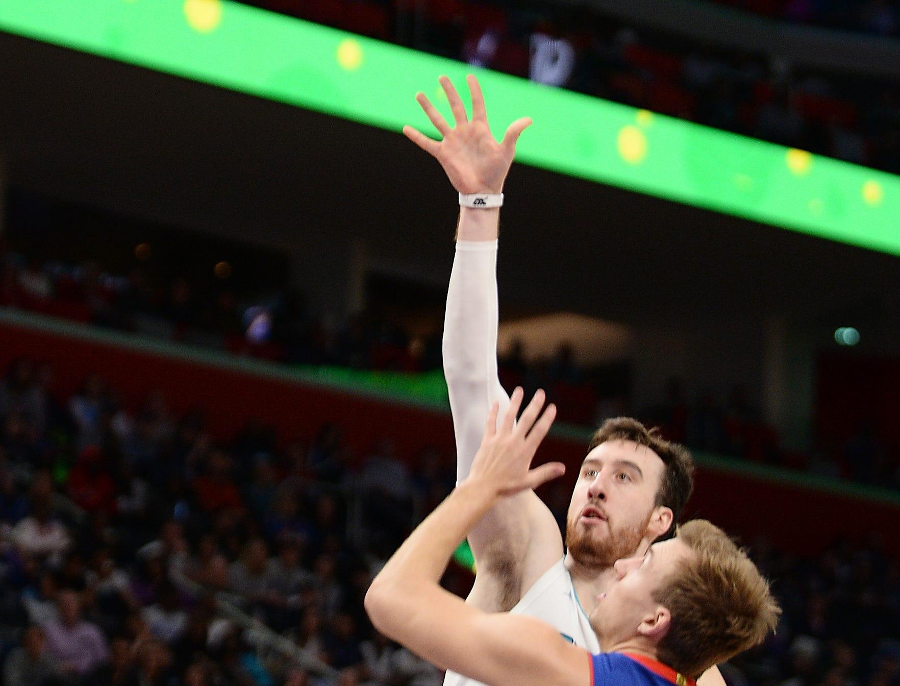 Hornets' Frank Kaminsky scores over Pistons' Luke Kennard in the fourth quarter.