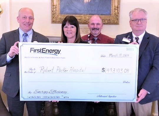 Penelec, a subsidiary of FirstEnergy Corp., presented Guthrie Robert Packer Hospital with a $500,000 check for energy efficiency upgrades. From left are hospital President Joseph Sawyer, FirstEnergy representative Jody Place, hospital director of facility operations Rennie Woodhouse and vice president of support services Michael Hogan.