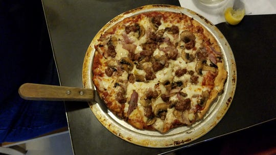 A pizza with ham, sausage and mushrooms from the Deerhead Sidewalk Cafe and Bar.