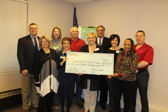 ProMedica Memorial Hospital donated a check to the Sandusky County Health Department for vacciine purchases. In front, from left, are Dorothy Kern, PMH Board; Dr. Iracema Arevalo, PMH Board; Bethany Brown, SCHD Health Commissioner; Joli Yeckley, Public Health Nurse; Regina Vincent- Williams, PMH and SCHD Board. In back, from left, are Bob Gross, SCHD Board; Pam Jensen and John Zimmerman, SCHD Board; Barry Luse, Vice Chair of PMH Board; and Tom Bowlus, PMH Board.