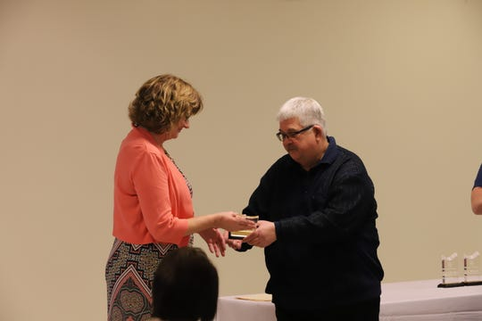 Clyde Mayor Scott Black presents a 10-year-service award to Council Clerk Janet Dickman.