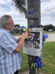Tom O'Brien, a friend of the Adam King family, helps take down a photo of King places on a tree on Colonial Blvd near where King was killed in a hit-and-run crash in June 2016. King's mother Tracy Miller vowed to remove the photo when a court case related to her sin's death was resolved. The case, involving James David Sinclair and evidence tampering was resolved Monday.