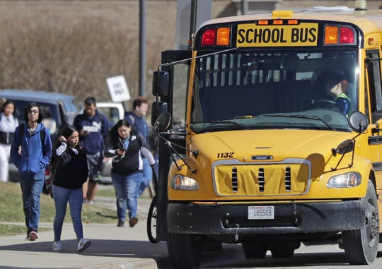 Students head to the school buses after class at Green Bay East High School.