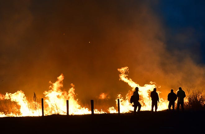 In this Sunday, April 7, 2019, photo Lame Deer, Mont., residents watch as a fire races across a field on the edge of town.
