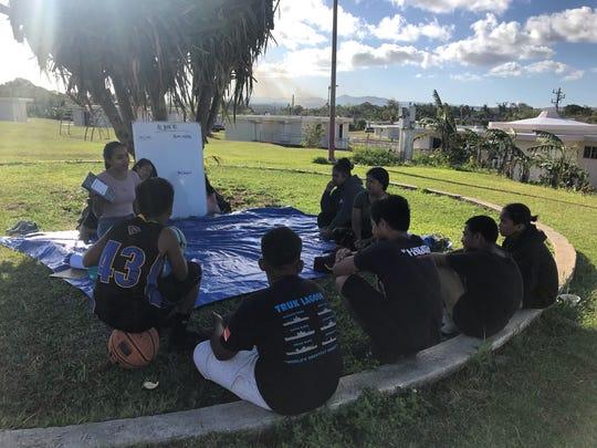 Kids in Mañe'lu's Art In the Ville art workshops listen during a spoken word workshop.