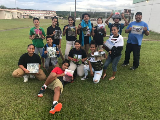 Participants in Mañe'lu's Art In the Ville art workshops pose with their finished products.