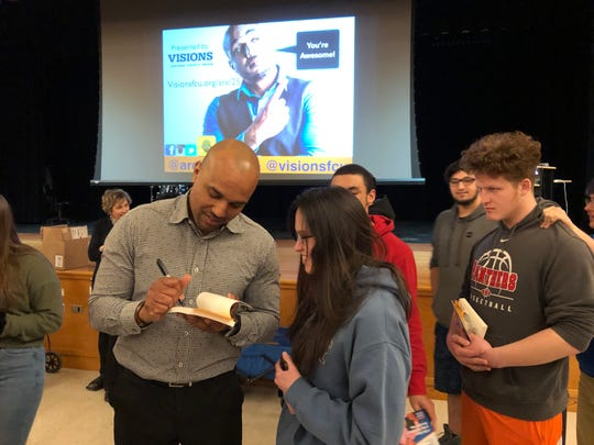 Arel Moodie signs a book for Chelsea Rossen as Christian Kunzman looks on. Moodie spoke to Spencer-Van Etten High School students about how to be a success in life.