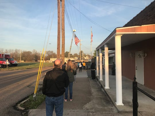 Spectators and volunteer pause for the National Anthem before the Andrew Jackson Marathon started on Lafayette Street in Downtown Jackson Saturday morning.