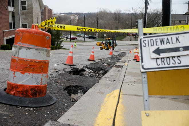 Crews work to fill damage from Sunday night's storm that washed away asphalt covering a newly laid gas line on East Wood st. between South Salisbury st. and South River road, Monday, April 8, 2019, in West Lafayette. (Nikos Frazier   The Journal & Courier)