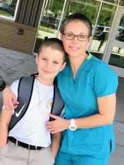 Colin McGee and mom Amy pose for a picture on Colin's first day of fifth-grade at Milton Elementary School. Colin, 11, was diagnosed with cancer about a month before school started, and his family and close friends shaved their heads with him before the first day of school.