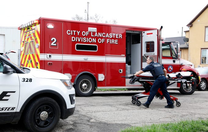 A Lancaster fire fighter pushes a stretcher toward the apartment building at 112 W. Walnut St. Monday morning, April 8, 2019, in downtown Lancaster.  One man died in the stabbing.