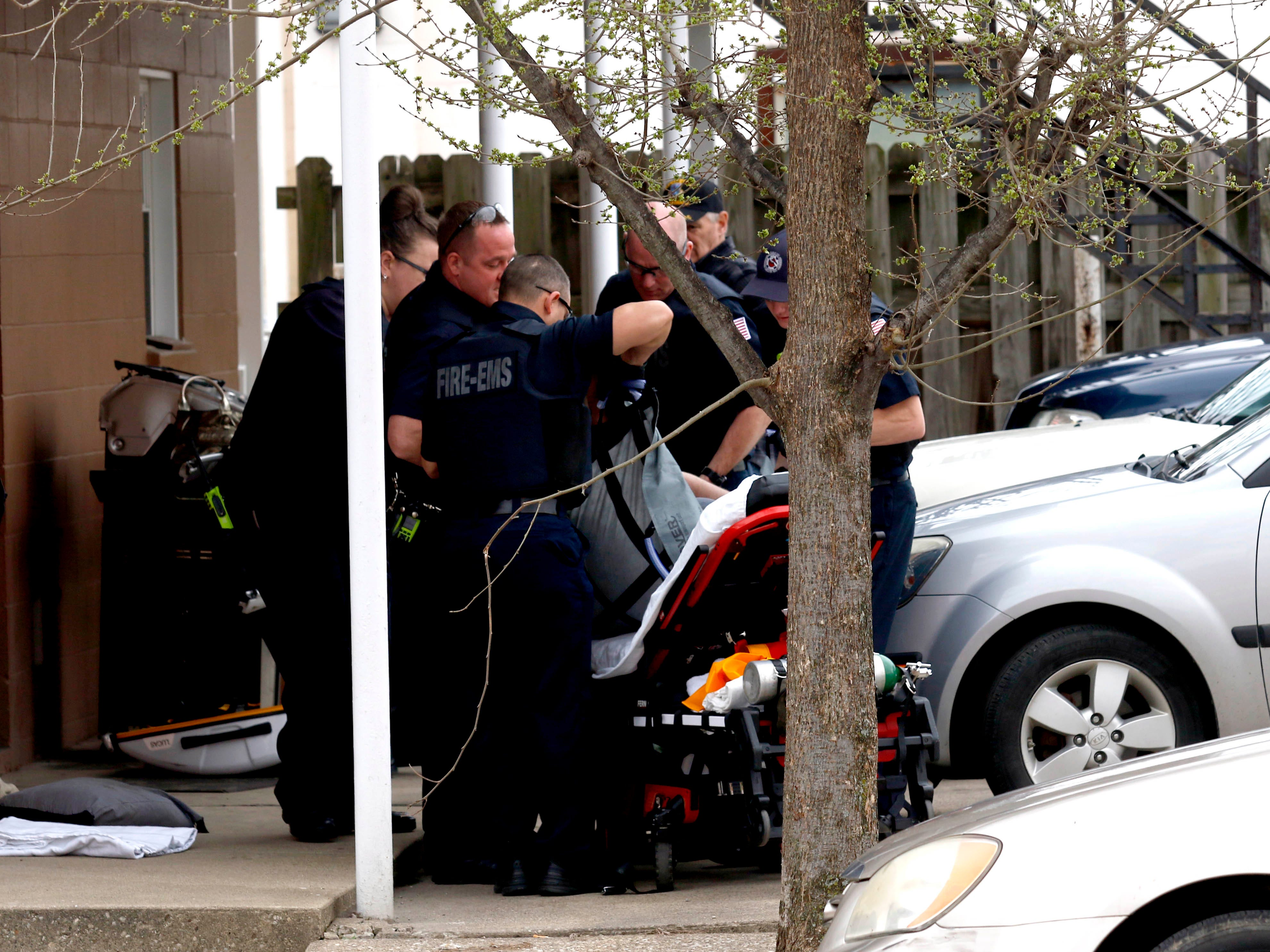 Lancaster fire fighters place a man on a stretcher Monday morning, April 8, 2019, in front of an apartment building at 112 W. Walnut Street in downtown Lancaster. One man died in the stabbing.