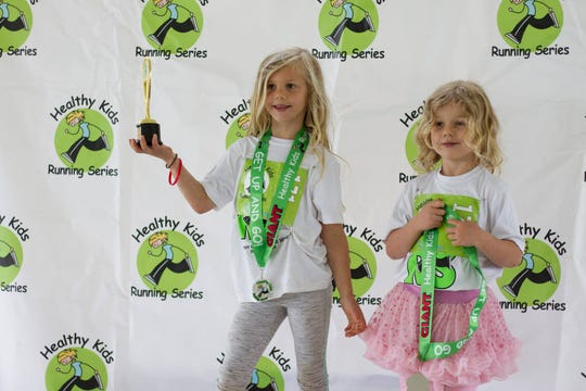 Gabrielle, 7, and Reese, 5, Desgrange pose with their medals after a 2018 Healthy Kids race.