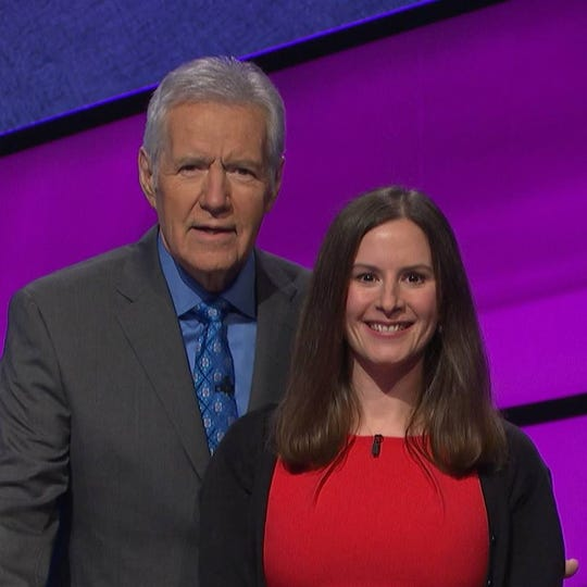 """Pinckney native Gabby McGregor will compete on the TV game show """"Jeopardy!"""" on Friday, April 19 in an episode that was taped in February in Culver City, California. Here McGregor stands next to host Alex Trebek in a complementary memento photo taken with each contestant after filming."""