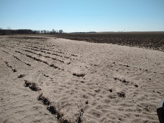 A layer of sand and silt covers a Nebraskan farm field. A team of farmers from North Central Ohio recently traveled to the Cornhusker State to help with cleanup efforts.
