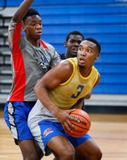 Academies of West Memphis High School standout basketball forward Chris Moore (right) drives to the basket against teammates during a recent practice.