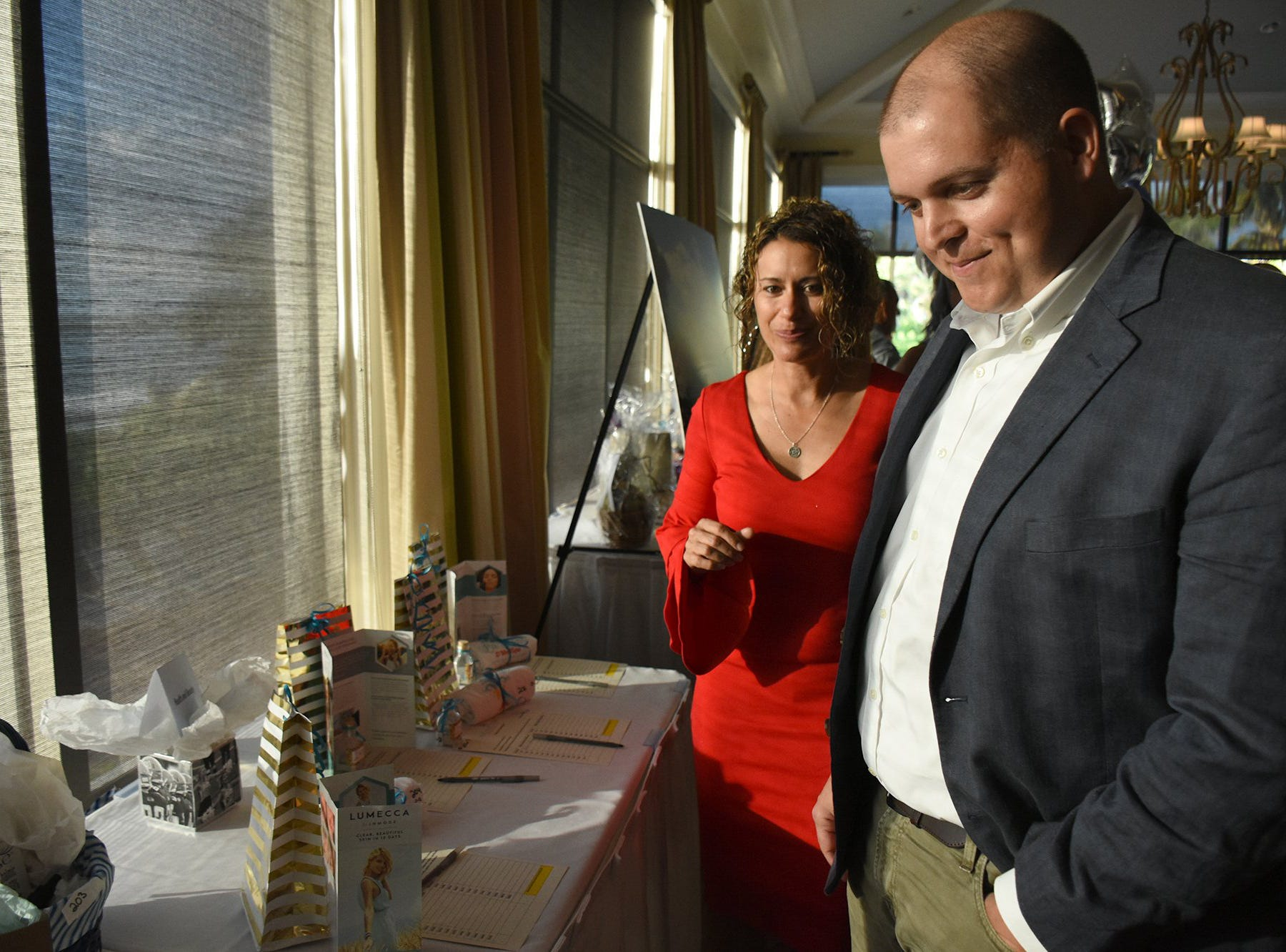 Cat and Paul Burke check out their bids in the silent auction. Marco Island Academy held 'Cheers for Champions,' a benefit dinner to raise funds for the school's athletic programs, Saturday evening at Hideaway Beach Club.