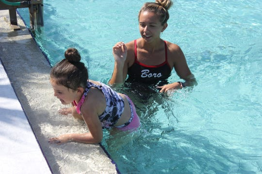 Aquatics Director Morgan Joseph works with a young swimmer at the Greater Marco Family YMCA pool.