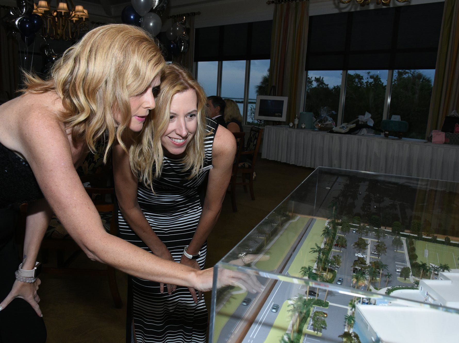 Melissa Scott, left, and Jane Watt inspect the newly unveiled architect's model. Marco Island Academy held 'Cheers for Champions,' a benefit dinner to raise funds for the school's athletic programs, Saturday evening at Hideaway Beach Club.