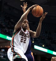 Milwaukee Bucks power forward Khris Middleton (22) gets past Phoenix Suns point guard Ish Smith (3) to score during the NBA basketball game between the Milwaukee Bucks and the  Phoenix Suns at the BMO Harris Bradley Center in Milwaukee, Wisconsin, Wednesday, January 29, 2014.